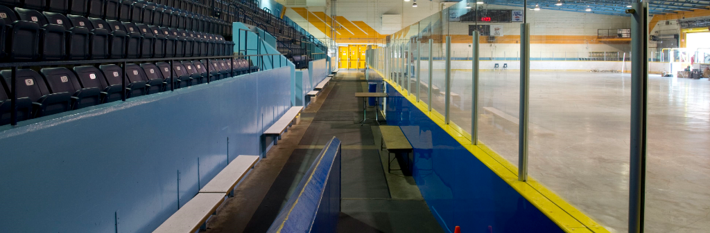 Picture showing seats, glass and ice rink inside an arena