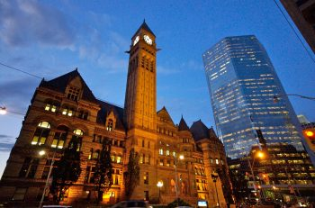 A view of Old City Hall at dusk from the Queen Street side and the facade illuminated with soft lighting.