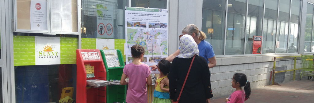 City Staff talking to a young family at a Don Mills Crossing pop-up engagement event.