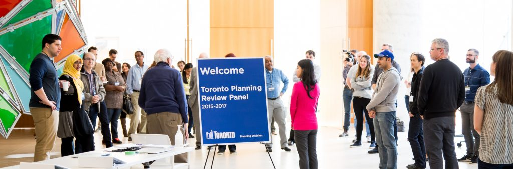 A sign welcomes Toronto Planning Review Panel members to their first meeting. Panel members are standing in the background