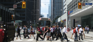 Image of a streetcar and pedestrians crossing through an intersection in the downtown core
