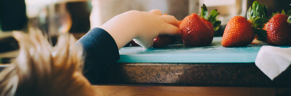 Boy reaching on the countertop for strawberries