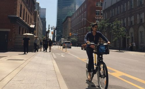 Image of cyclist using designated bike lane and wide sidewalks on Simcoe Street.