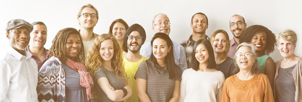 A group of multicultural people of all ages smiling at camera