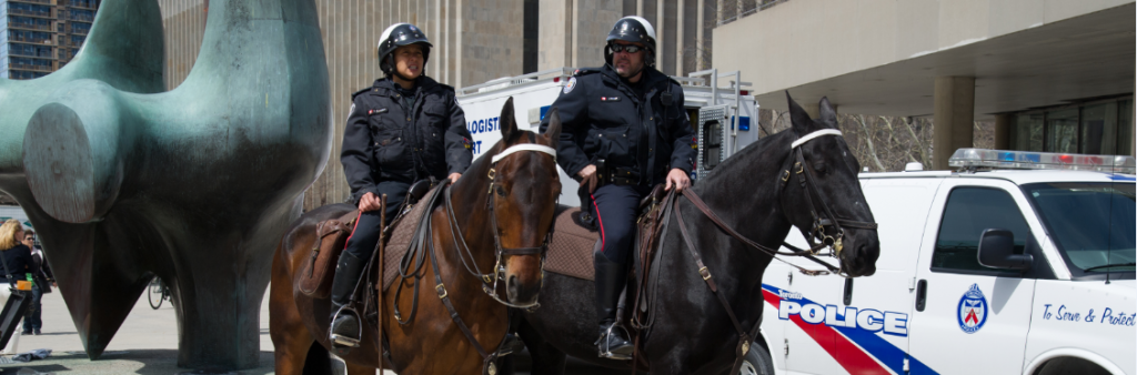 Two uniformed officers on horseback with police car in background.