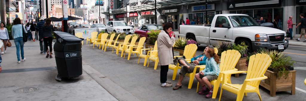 Image of Yonge Street near Dundas square with yellow patio chairs on the curbside lane