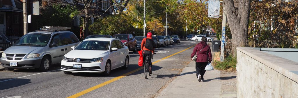 Cyclist heading northbound in the contraflow lane along Bellevue with a car going the opposite direction.