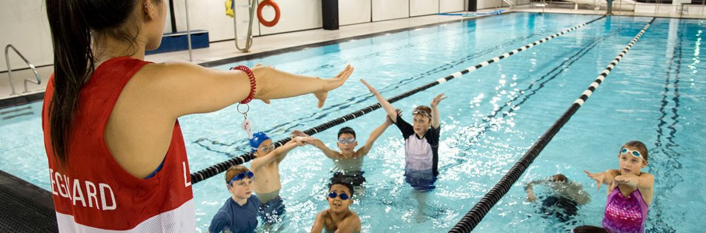A swim instructor on the pool deck instructs children in the water at an indoor pool