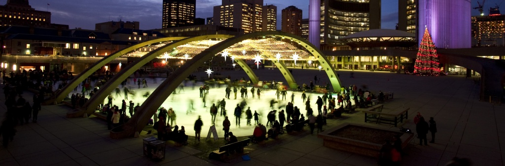 People skating at night in Nathan Phillips Square.