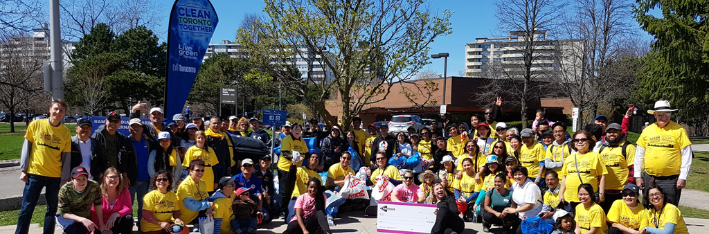 A photograph showing a group of Clean Toronto Together volunteers. Volunteers are posing for a picture, wearing yellow shirts.