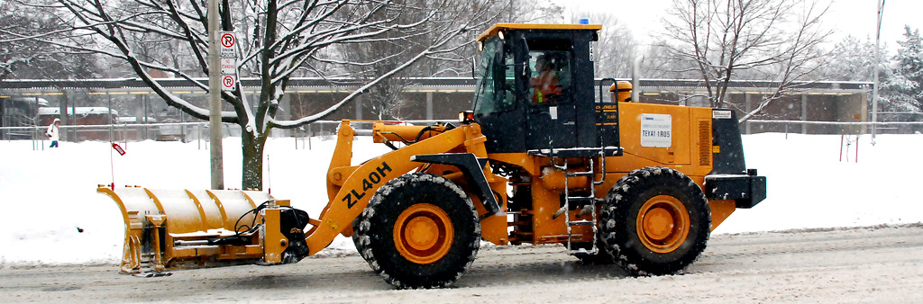 Photograph of a yellow snow plow removing snow from a road.