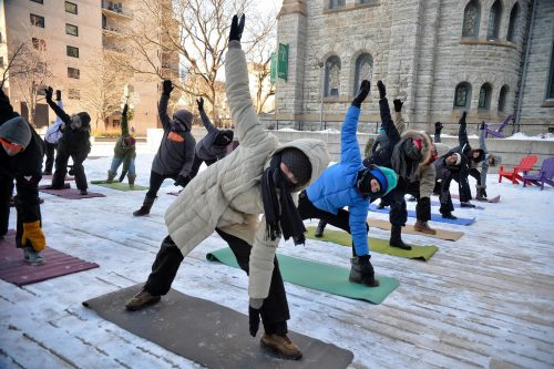 Yoga in Minneapolis: 9 people doing yoga outdoors during winter.