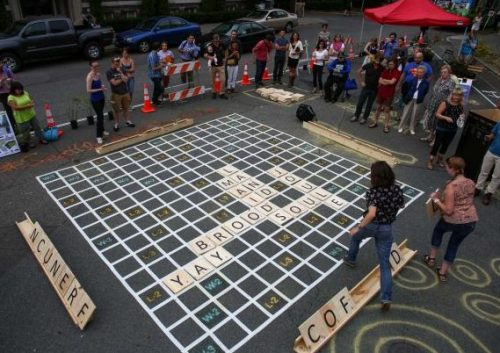Giant Scrabble, Seattle: 3 people playing a giant scrabble on the street with 20 people watching.