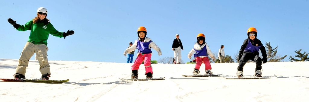 An instructor and students snowboarding downhill