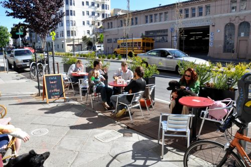 Public Seating, San Francisco: 5 people and a dog seated at 3 red café tables with aluminium metal chairs.