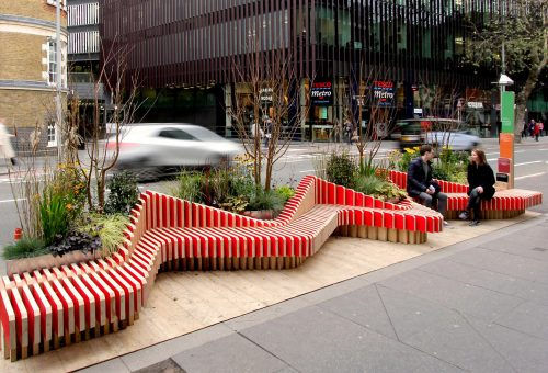Tooley Street, London: Parklet - wooden zigzag bench with trees and shrubs.