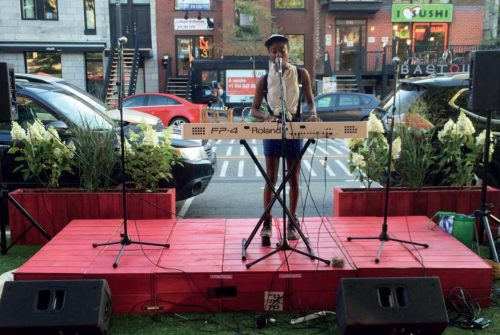 La Grande Terrasse Rouge, Montreal: Singer with keyboard on a parklet stage with 3 microphones.
