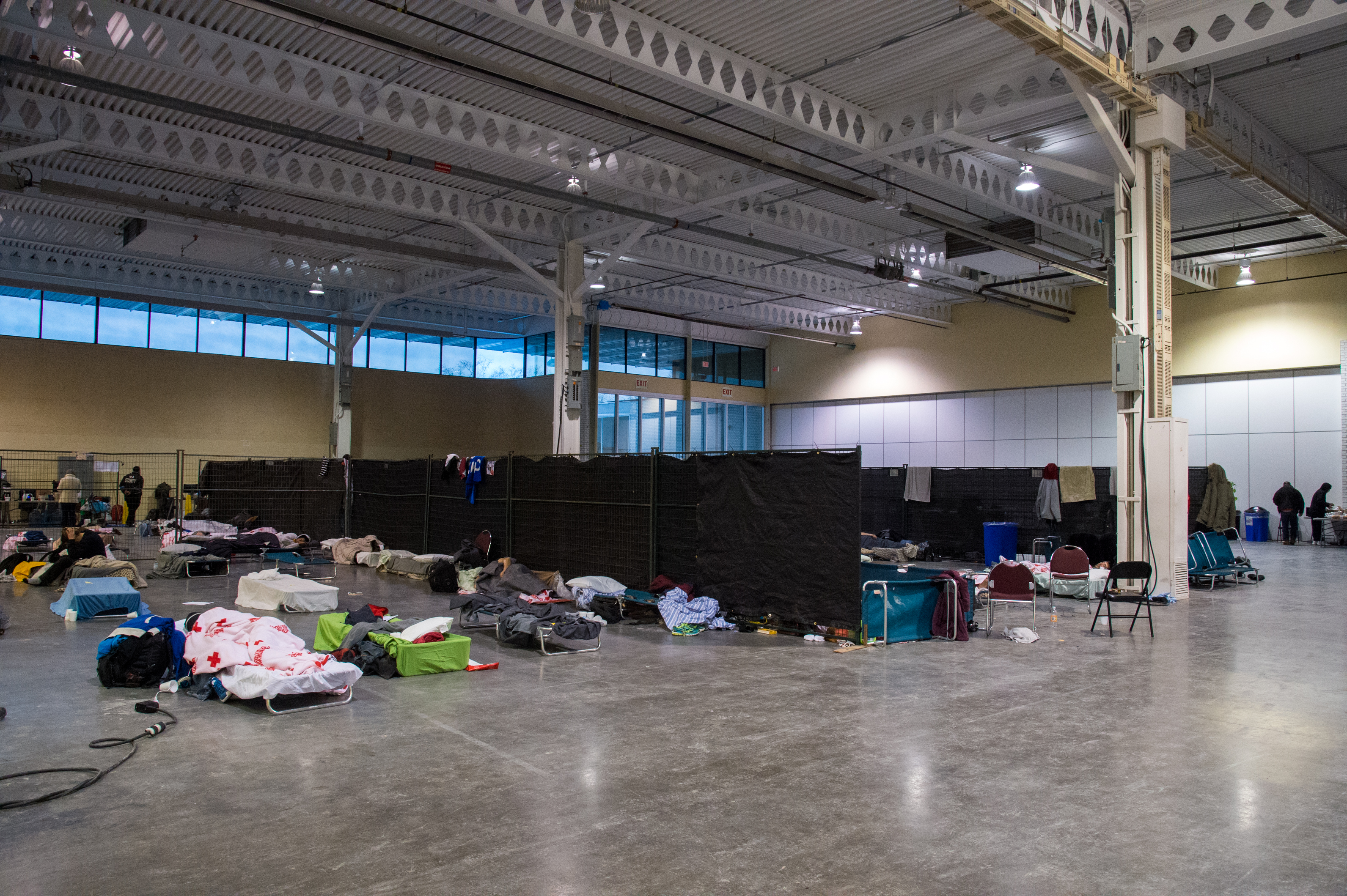 Photo of the interior of the Better Living Centre at Exhibition Place showing cots in a open area divided by curtain walls
