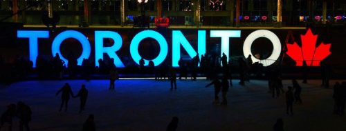 Toronto Sign at night with skaters on rink