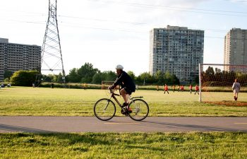 Cyclist on path by soccer field