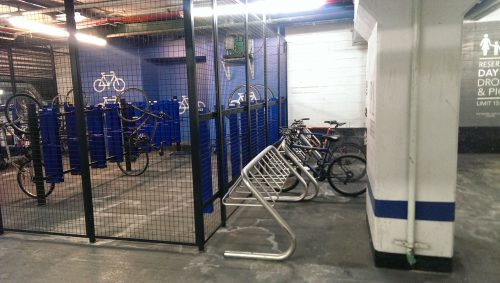Long term bicycle parking located in the garage of an office building. A secure bicycle cage is located beside some bicycle racks.