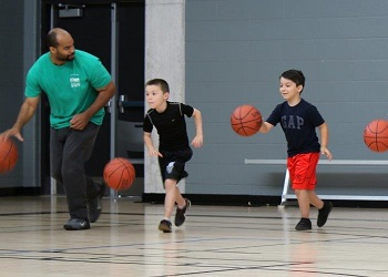 Camp counsellor playing basketball in a gym with two children