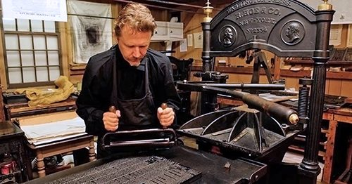 Printing press operator in historic costume