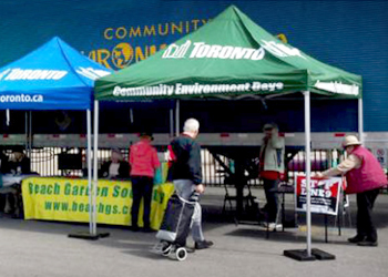 People dropping off material at an outdoor tent at a Community Environment Day event