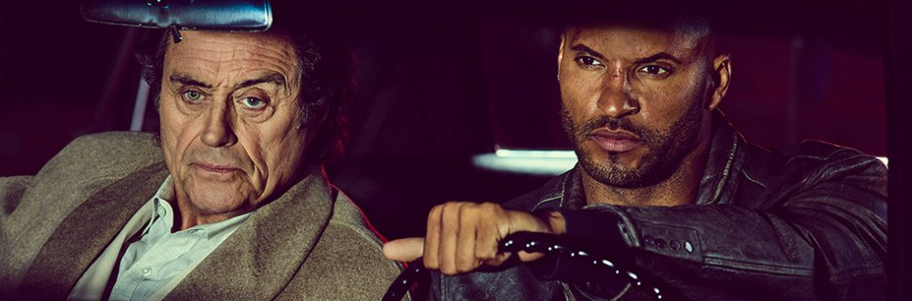two actors in a driving scene from the television series American Gods