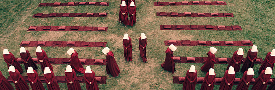 group of women dressed in red gowns and white head coverings standing in a field