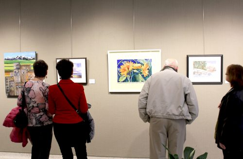 Four visitors to the gallery looking at paintings
