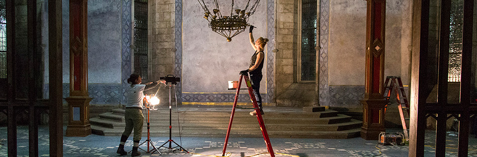 woman standing on step ladder painting a chandelier