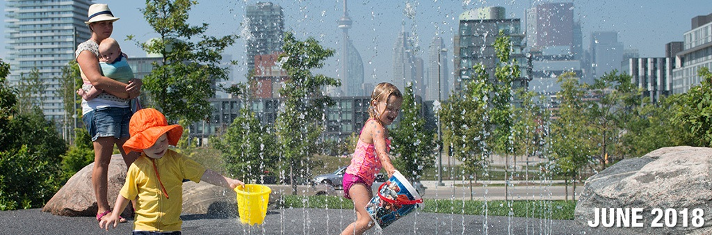 A young girl and boy play in a City splash pad as their mother watches holding their baby brother. The City skyline is in the background.