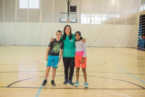 An instructor stands with a boy and girl on a basketball court