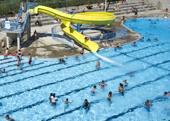 Outdoor pool filled with children on a sunny summer day