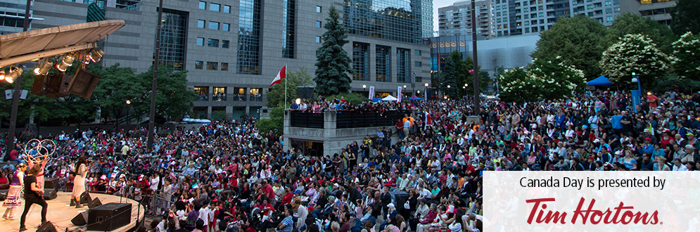 Image of the Canada Day celebrations at Mel Lastman Square in 2017. Showing a concert, crowd and sponsor logo at the bottom stating: Canada Day is presented by Tim Hortons.