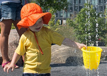 An image of a little boy in an orange sun hat playing in a splash pad
