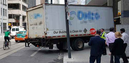 Cyclist avoiding truck turning into loading dock elevator on the right side of Adelaide Street