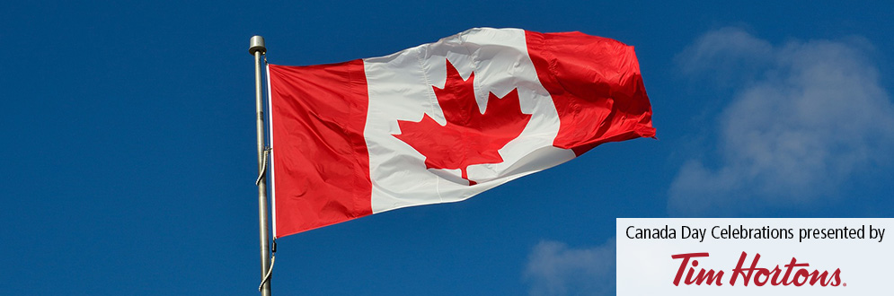 Canadian flag flying in breeze in front of blue sky with Tim Hortons logo and teh words Canada Day presented by