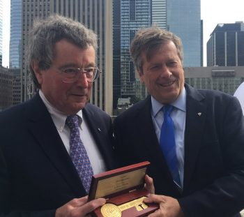 Paul Beestong and Mayor John Tory hold a key to the city on the Toronto City Hall Green Roof.