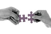 Two hands holding puzzle pieces that fit together