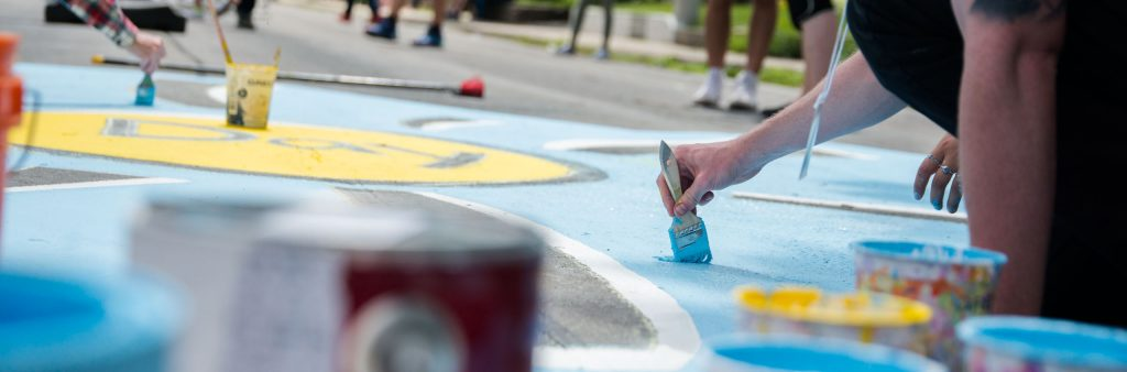 Person painting with blue paint on the road