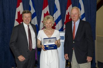Judy Matthews holds key to the City while smiling for cameras with husband Wilmot and Mayor John Tory at City Hall.