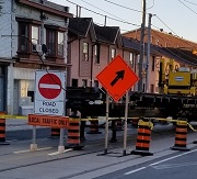 City street with a road closed sign and construction equipment