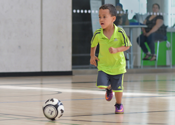 boy playing indoors with a soccer ball at a City of Toronto recreation centre