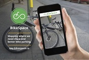 A hand holding a cellphone with the BikeSpace app open on it