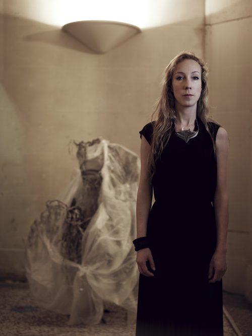 Image info: Iris van Herpen, courtesy Jean Baptiste Mondino and Iris van Herpen. Artist with dress exhibit in background.