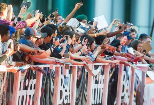 Excited fans outside of TIFF movie - behind crowd barricades.