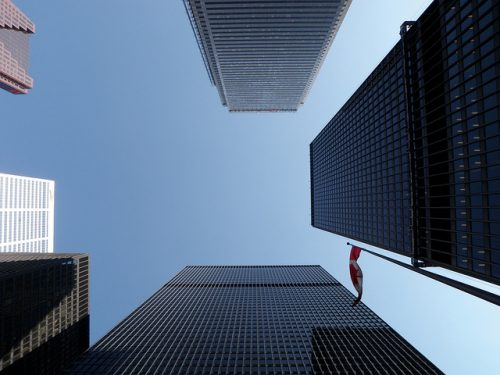 looking up at sky from the ground, between 6 buildings, Canadian Flag.