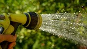 Close up image of a hose with water spouting out of it